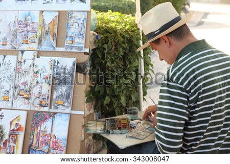 LISBON PORTUGAL-OCTOBER 8, 2015:  Painter at Santa Luzia outlook in Alfama quarter Lisbon Portugal - stock photo