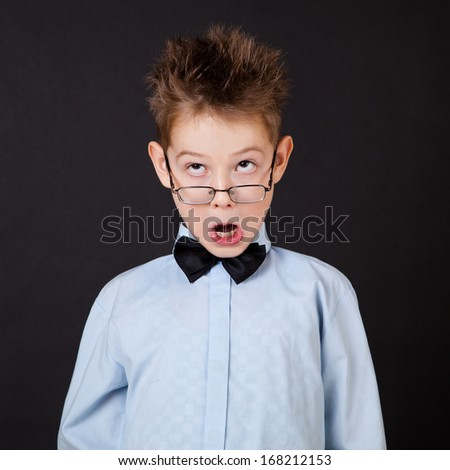 Little boy with funny face on black background - stock photo