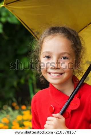Little cute girl in a red jacket holding an umbrella - stock photo