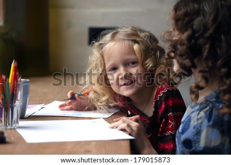 little girl drawing and looking at the camera  - stock photo