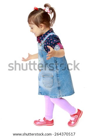 Little girl in a denim dress on white background - isolated on white background - stock photo