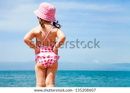 little girl in a swimming suit looks at the sea - stock photo