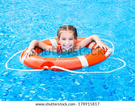 little girl in the pool floating on the Lifebuoy - stock photo
