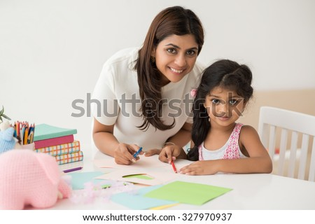 : Little girl making greeting card with her mother - stock photo