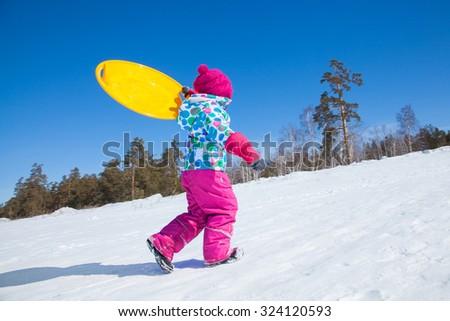 little girl running on snow  in winter - stock photo