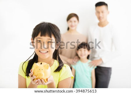 little girl showing the piggy bank and family finance concept - stock photo