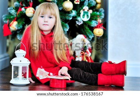 little girl sits on the floor near the Christmas tree - stock photo