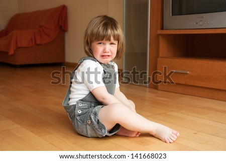 little girl sitting on the floor and crying - stock photo