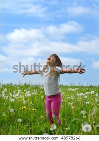 little girl standing with outstretched arms, she enjoying summer - stock photo