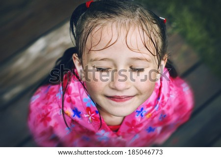 Little girl with eyes closed stands after  the rain in the garden. - stock photo
