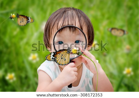 little girl with magnifying glass outdoors in the day time - stock photo