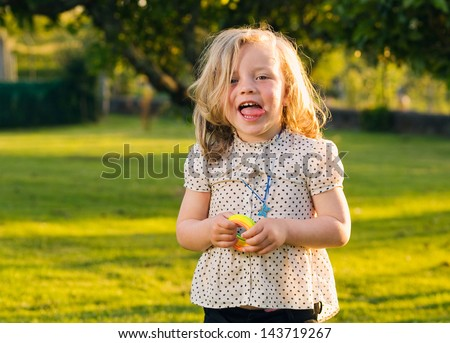 Little girl with naughty expression. The girl is sticking her tongue out and her expression is funny. - stock photo