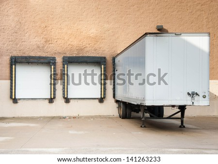 Loading docks and the semi truck trailer transferring cargo in the industrial area or for departmental store. Where is the cargo?  - stock photo