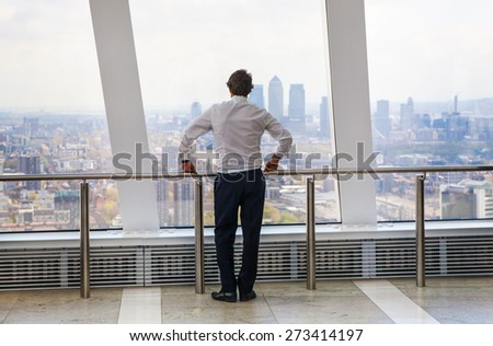 LONDON, UK - APRIL 22, 2015: Businessman looking at London through the window of Walkie-Talkie building. View includes Canary Wharf business and banking aria. Business concept image - stock photo