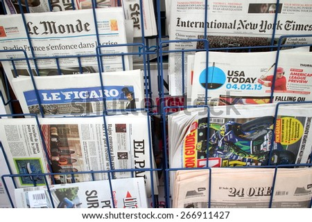 London, United Kingdom - April 02, 2015: International and Foreign Language newspapers including Le Monde, USA Today and Le Figaro on display in a rack outside a store. - stock photo