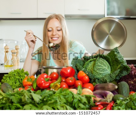 long-haired housewife cooking with fresh vegetables at home kitchen - stock photo