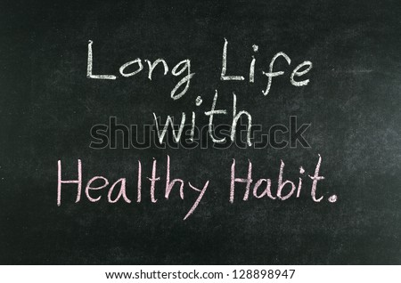 """long life with healthy habit"" word written on blackboard - stock photo"