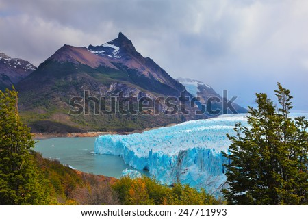 Los Glaciares National Park in Patagonia. Huge Perito Moreno glacier in the Lake Argentino, surrounded by mountains. Sunny summer day - stock photo