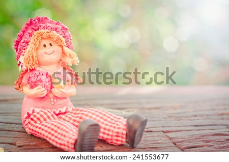 Lovely doll sitting on a wooden and bokeh background in a vintage retro style, with the sunrise, for the day of love, Valentine's Day. - stock photo