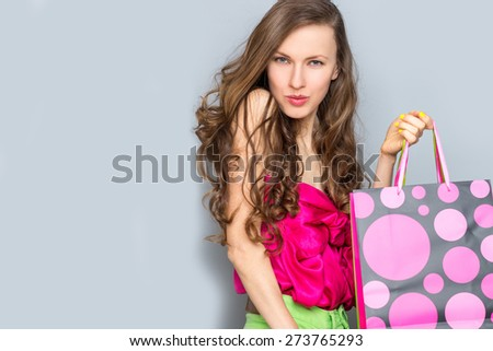 Lovely woman with shopping bags over grey - stock photo