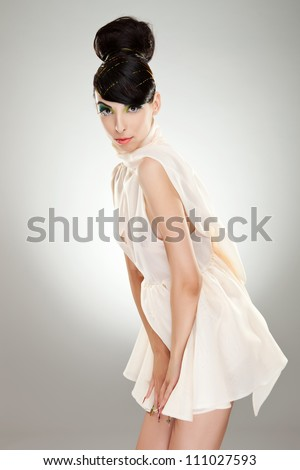 lovely young woman in fashion white dress looking at the camera and holding hands near crotch zone. on gray background - stock photo