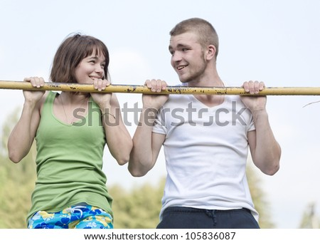 Loving couple hanging on the crossbar - stock photo