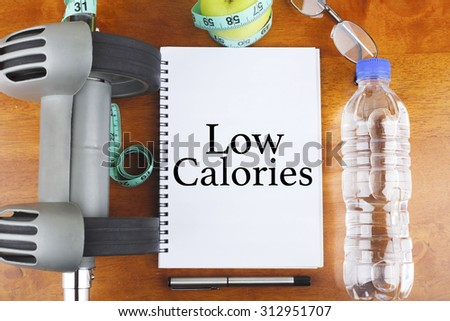 """""""Low Calories"""" text on notebook with delicious green apple, measure tape, spectacle, a bottle of mineral water, and bodybuilding tools on wooden background - healthy, exercise and diet concept - stock photo"""