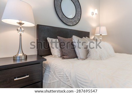 Luxury bedroom. Contemporary design with reclaimed wood bedside tables and lamp. Nice and cozy accommodations. Hotel or resort room. - stock photo