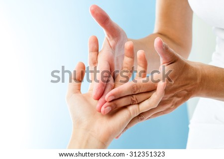 Macro close up of therapist hands doing curative massage on female hand. - stock photo