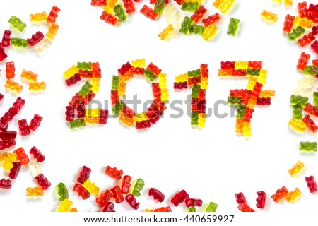 2017 made from colorful gummy bears and more gums around as a happy New Year greeting card, isolated with small shadows on a white background