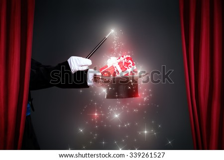 Magician hand with magic wand making Christmas  gift, Christmas spell - stock photo