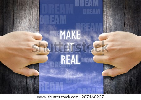 """""""Make it real"""" text in the sky behind 2 hands opening the wooden door. - stock photo"""