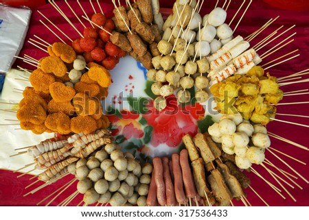 Malaysian fast food like fish balls,  fried chicken, deep-fried potato, sausages and meat balls selling at sunday market. Selective focus with shallow depth of field.   - stock photo
