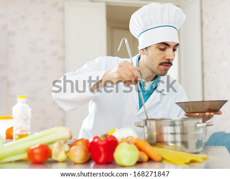 male cook with ladle pours soup from pan to plate at kitchen - stock photo