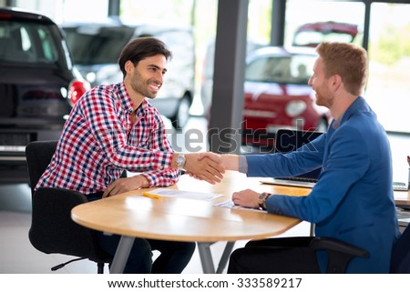 Man at a car dealership buying an auto, car agent handshake with his client  - stock photo