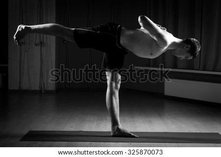man does yoga in sports hall - stock photo