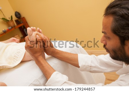 Man giving a foot massage  for a client in relaxing spa environment . - stock photo