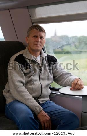 man goes in a train near a window - stock photo