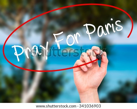 Man Hand Pray for Paris with marker on visual screen. Isolated on nature.  - stock photo