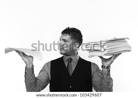 man holding a lot of paper work up in the air a pile in each hand - stock photo