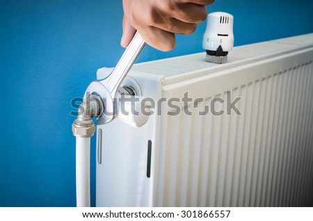 Man installing radiator valve close up - stock photo
