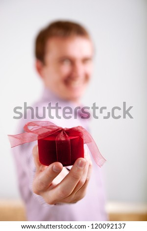 Man proposing by holding out a beautiful red ring box towards the camera. Selective focus on hands and ring box. - stock photo