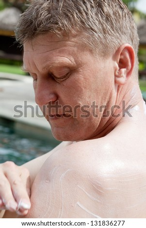 man puts on skin protective cream from the sun - stock photo