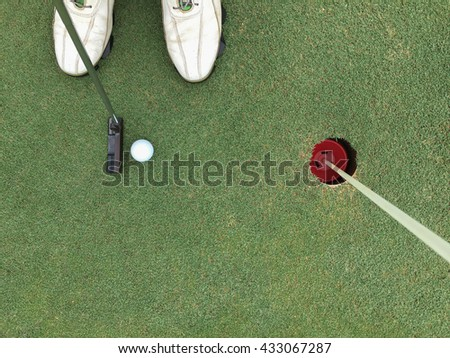 man putts a golf ball to the hole - stock photo