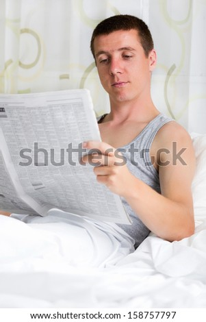 man reading a newspaper in his bedroom  - stock photo