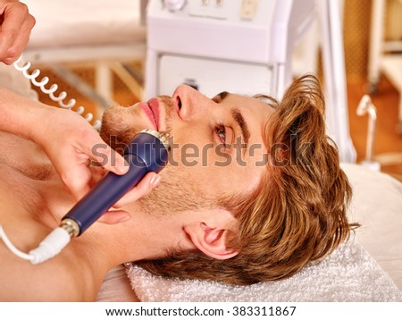 Man's head on electroporation  facial therapy at beauty salon.  - stock photo