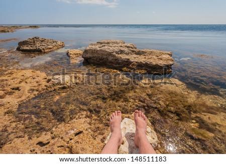 man sitting on the rocks near the ocean - stock photo