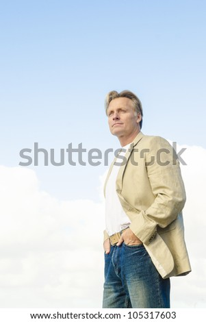 man standing in profile wearing a beige colored jacket and a white t'shirt - stock photo