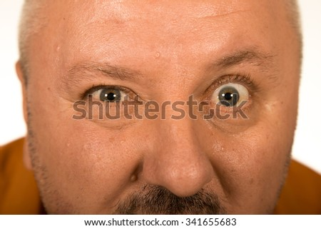 Man with big eyes staring at you over white background - stock photo