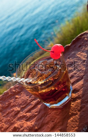 Manhattan cocktail garnished with a cherry. Cocktail against sea Outdoor composition during sunset lights - stock photo